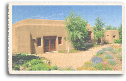 An adobe home features a xeriscape landscaping to conserve water use in the high desert of New Mexico.